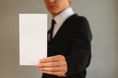 offset views: Business man showing blank white flyer brochure booklet. Leaflet presentation. Pamphlet hold hands. Man show clear offset paper. Sheet template. Booklet design sheet display read first person