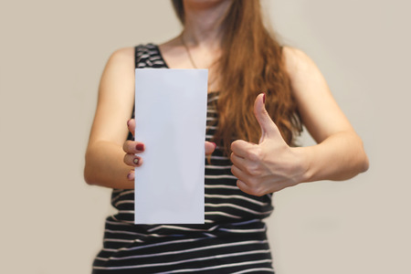 offset up: Girl showing blank white flyer brochure booklet. Leaflet presentation. Pamphlet hold hands. Woman show clear offset paper. Sheet template. Booklet design sheet display read first person. Thumbs up