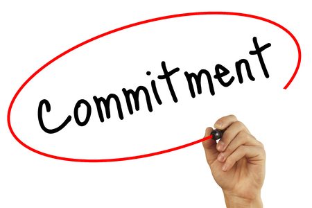 Man Hand writing Commitment with black marker on visual screen. Isolated on background. Business, technology, internet concept. Stock Photo