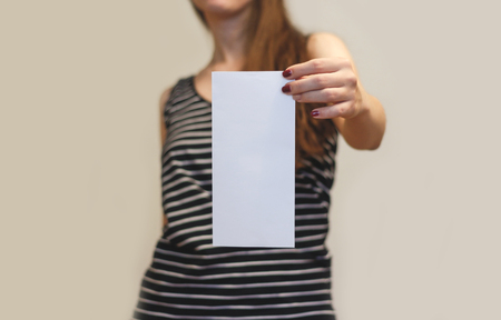 offset up: Girl showing blank white flyer brochure booklet. Leaflet presentation. Pamphlet hold hands. Woman show clear offset paper. Sheet template. Booklet design sheet display read first person