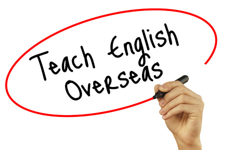 Man Hand writing Teach English Overseas with black marker on visual screen. Isolated on background. Business, technology, internet concept. Stock Photo