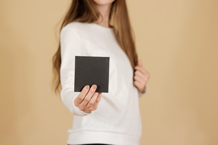 offset views: Girl showing blank black square flyer brochure booklet. Leaflet presentation. Pamphlet hold hands. Woman show clear offset paper. Sheet template. Booklet design sheet display read first person