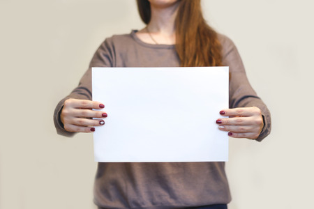 offset views: Girl holding white A4 blank paper horizontally. Leaflet presentation. Pamphlet hold hands. Woman show clear offset paper. Sheet template. Booklet design sheet display read first person. Stock Photo
