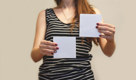 offset views: Girl showing two blank white square flyer brochure booklet. Leaflet presentation. Pamphlet hold hands. Woman show clear offset paper. Sheet template. Booklet design sheet display read first person