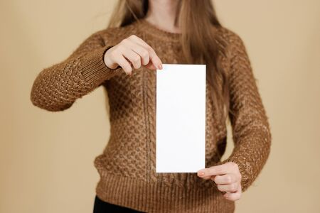 note booklet: Girl showing blank white flyer brochure booklet. Leaflet presentation. Pamphlet hold hands. Woman show clear offset paper. Sheet template. Booklet design sheet display read first person