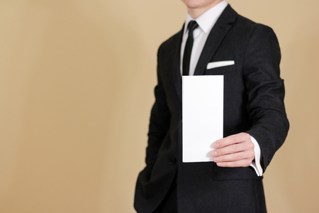 offset views: Man showing blank black flyer brochure booklet. Leaflet presentation. Pamphlet hold hands. Man show clear offset paper. Sheet template. Man in a black suit, white shirt and tie.