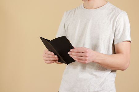 offset views: Man showing blank black flyer brochure. Read booklet. Leaflet presentation. Pamphlet hold hands. Man show clear offset paper. Sheet template. Booklet design sheet display read first person Stock Photo