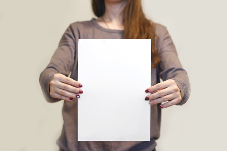 offset views: Girl holding white A4 blank paper vertically. Leaflet presentation. Pamphlet hold hands. Woman show clear offset paper. Sheet template. Booklet design sheet display read first person. Stock Photo
