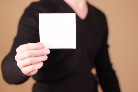 offset views: Man showing blank white square flyer brochure booklet. Leaflet presentation. Pamphlet hold hands. Man show clear offset paper. Sheet template. Booklet design sheet display read first person Stock Photo