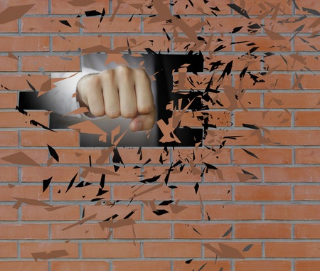smithereens: Fist smashes a brick wall to smithereens. Man hand breaking wall.