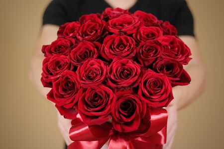 Man in black t shirt holding in hand rich gift bouquet of 21 red roses. Composition of flowers in a white hatbox. Tied with wide red ribbon and bow. Stock Photo