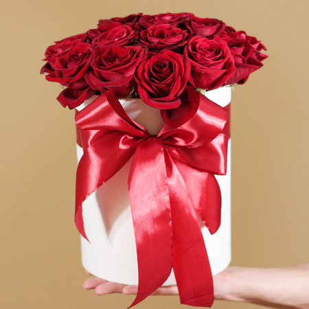 Man hand holding rich gift bouquet of 21 red roses. Composition of flowers in a white hatbox. Tied with wide red ribbon and bow.