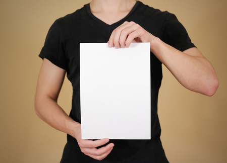 offset views: Man in black t shirt holding blank white A4 paper. Leaflet presentation. Pamphlet hold hands. Man show clear offset paper. Sheet template. Stock Photo
