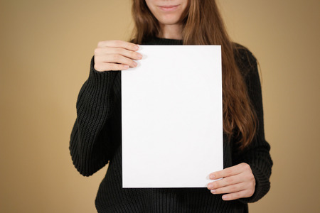 offset views: Girl holding white A4 blank paper. Leaflet presentation. Pamphlet hold hands. Woman show clear offset paper. Sheet template. Booklet design sheet display read first person. Stock Photo