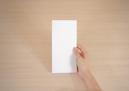 offset view: Hands holding blank white brochure booklet in the hand. Leaflet presentation. Pamphlet hand man. Show offset paper. Sheet template. Book in hands. Booklet folding design. Fold paper sheet display read Stock Photo