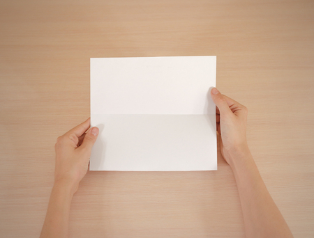 offset up: Hands holding blank white brochure booklet in the hand. Leaflet presentation. Pamphlet hand man. Show offset paper. Sheet template. Book in hands. Booklet folding design. Fold paper sheet display read Stock Photo