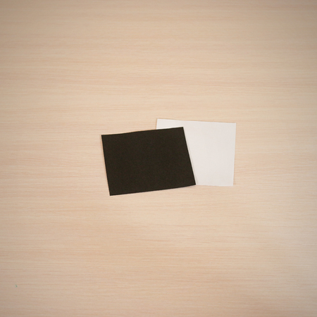 offset views: Two blank square paper. White and black note. Leaflet blank white paper brochure mockup on a wooden table. Show offset paper. Sheet template. Book in hands. Booklet folding design. Fold paper sheet display read