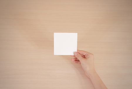 offset views: Right hand holding square white paper in the right hand. Leaflet presentation.