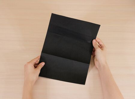 offset views: Hands holding blank black brochure booklet in the hand. Leaflet presentation. Pamphlet hand man. Show offset paper. Sheet template. Book in hands. Booklet folding design. Fold paper sheet display read. Stock Photo