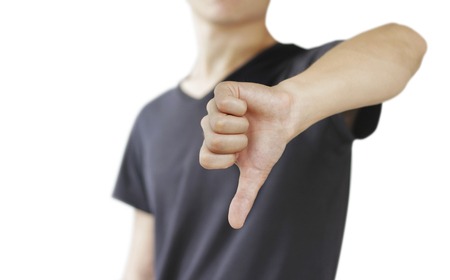 Young man in black t shirt showing a sign of dislike, isolated on a white background.