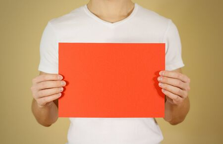 offset views: Man holding red A4 paper horizontally. Leaflet presentation. Pamphlet hold hands. Man show clear offset paper. Sheet template. Booklet design sheet display read first person Stock Photo