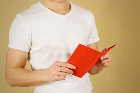 offset views: Man reading blank red flyer brochure. Read detailed booklet. Leaflet presentation. Pamphlet hold hands. Man show clear offset paper. Sheet template. Booklet design sheet display read first person Stock Photo
