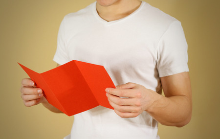 Man reading blank red flyer brochure. Read detailed booklet. Leaflet presentation. Pamphlet hold hands. Man show clear offset paper. Sheet template. Booklet design sheet display read first person Stock Photo