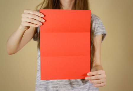 offset up: Girl showing blank red flyer brochure booklet. Leaflet presentation. Pamphlet hold hands. Woman show clear offset paper. Sheet template. Booklet design sheet display read first person