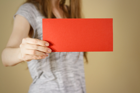 offset views: Girl showing blank red flyer brochure booklet. Leaflet presentation. Pamphlet hold hands. Woman show clear offset paper. Sheet template. Booklet design sheet display read first person