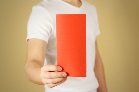 offset views: Man showing blank red flyer brochure booklet. Leaflet presentation. Pamphlet hold hands. Man show clear offset paper. Sheet template. Booklet design sheet display read first person