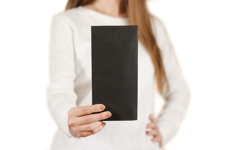 note booklet: Girl showing blank black flyer brochure booklet. Leaflet presentation. Pamphlet hold hands. Woman show clear offset paper. Sheet template. Booklet design sheet display read first person. On white. Stock Photo