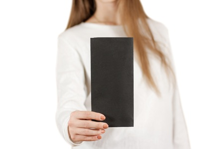 offset views: Girl showing blank black flyer brochure booklet. Leaflet presentation. Pamphlet hold hands. Woman show clear offset paper. Sheet template. Booklet design sheet display read first person