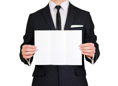 offset views: Man showing blank black flyer brochure booklet. Leaflet presentation. Pamphlet hold hands. Man show clear offset paper. Sheet template. Man in a black suit, white shirt and tie. On white background Stock Photo