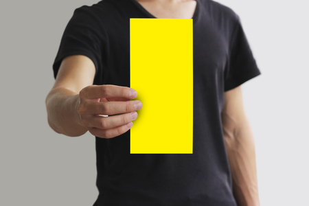 offset views: Man showing blank yellow flyer brochure booklet. Leaflet presentation. Pamphlet hold hands. Man show clear offset paper. Sheet template. Booklet design sheet display read first person