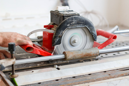 Man tiler construction worker electric porcelain cuts tiles Tile. Working with decorative tile cutting equipment at repair renovation work.