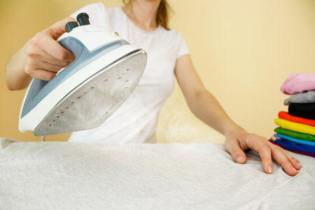 Closeup of woman ironing colored clothes on ironing board. Housewife uses the home appliance. Steam iron.