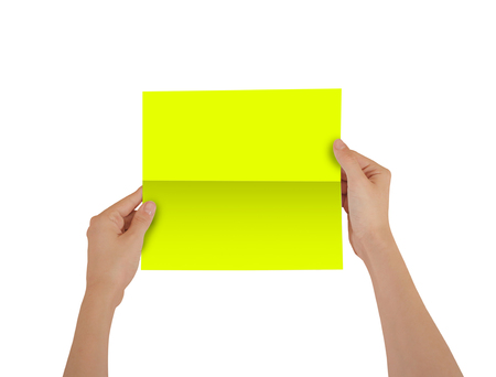 offset view: Hands holding blank yellow brochure booklet in the hand. Leaflet presentation. Pamphlet hand man. Show offset paper. Sheet template. Book in hands. Booklet folding design. Fold paper sheet display read Stock Photo