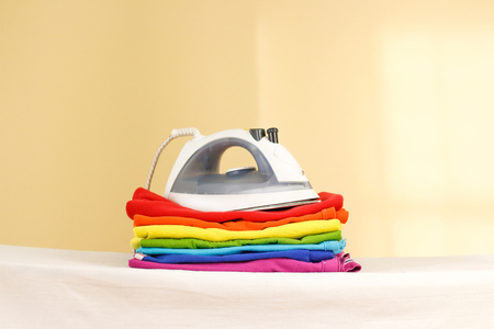 Iron stands with stacks of ironed colored linen. Pile of clothes. Ironing concept. All colors of the rainbow