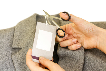 Girl hands removing cutting label board price tag off grey wool coat with scissors. Female after shopping