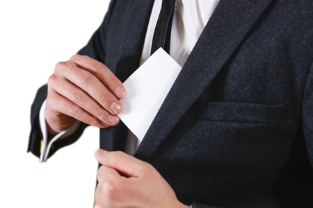 offset up: Businessman putting paper in suit pocket closeup. Showing blank flyer brochure booklet. Pamphlet hold hands. Show clear offset paper. Sheet template. Man in a black suit, white shirt and tie.