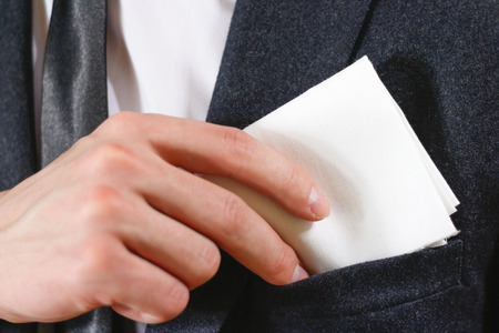 Close up hand puts a white handkerchief in the pocket of his black jacket.