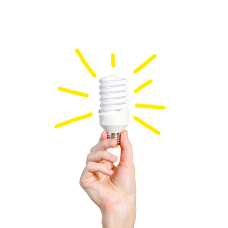 Closeup of mans hand holding energy saving lamp. Bright yellow rays. Outgoing painted yellow rays. Isolated on white background. Stock Photo