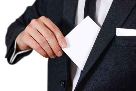 offset up: Businessman putting paper in suit pocket closeup. Showing blank flyer brochure booklet. Pamphlet hold hands. Show clear offset paper. Sheet template. Man in a black suit, white shirt and tie Stock Photo