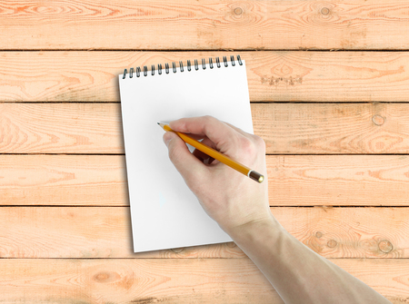 empty handed: Right hand writing on notebook with white background. Top view of work desk. On a wooden table Stock Photo
