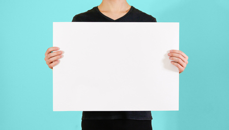 offset up: Man showing blank white big A2 paper. Leaflet presentation. Pamphlet hold hands. Man show clear offset paper. Sheet template. Booklet design sheet display read first person Stock Photo