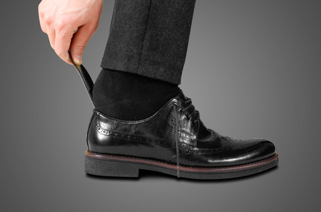 Wearing black shoes with a spoon. Isolated on white background.