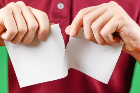 Man tearing a piece of paper in half blank white flyer brochure booklet. Leaflet presentation. Pamphlet hold hands. Male show clear offset paper. Sheet template. Booklet design sheet display. Banque d'images