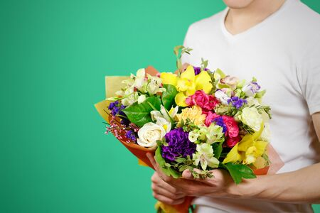 big shirt: Young guy in a white shirt holding a beautiful bouquet of flowers. Isolated.