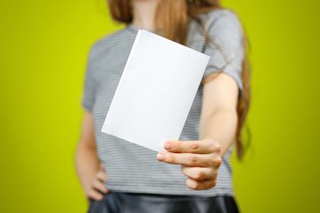 Vrouw die leeg wit vliegerdocument toont. Folderpresentatie. Pamflet houdt de handen vast. Meisje toont duidelijk offsetpapier. Blad sjabloon. Boekje ontwerp vel display lees eerste persoon. Stockfoto