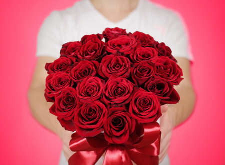 Man in white t shirt holding in hand rich gift bouquet of 21 red roses. Composition of flowers in a white hatbox. Tied with wide red ribbon and bow.